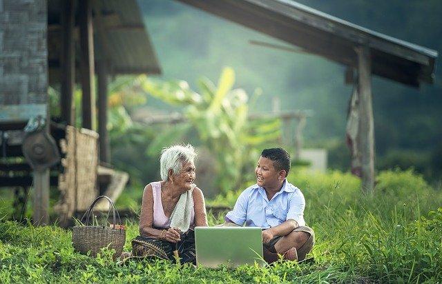 Babka a dieťa sedia za počítačom uprostred lúky